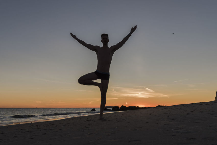 Silhouetted man doing a yoga pose tree stand with arms raised up at sunset on the beach Yoga Yoga Pose Arms Raised Balance Beach Beauty In Nature Exercising Flexibility Full Length Healthy Lifestyle Leisure Activity Lifestyles Nature One Person Outdoors Practicing Real People Sand Sea Sky Tree Pose Water Young Adult Zen