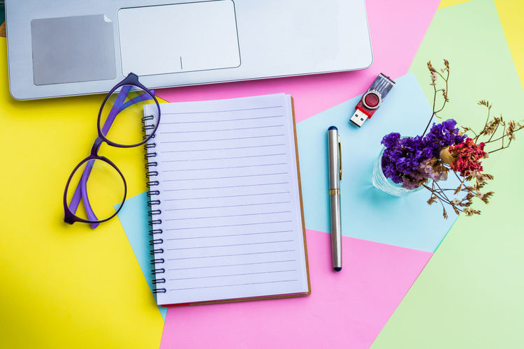 Spiral notebook with laptop on colorful papers