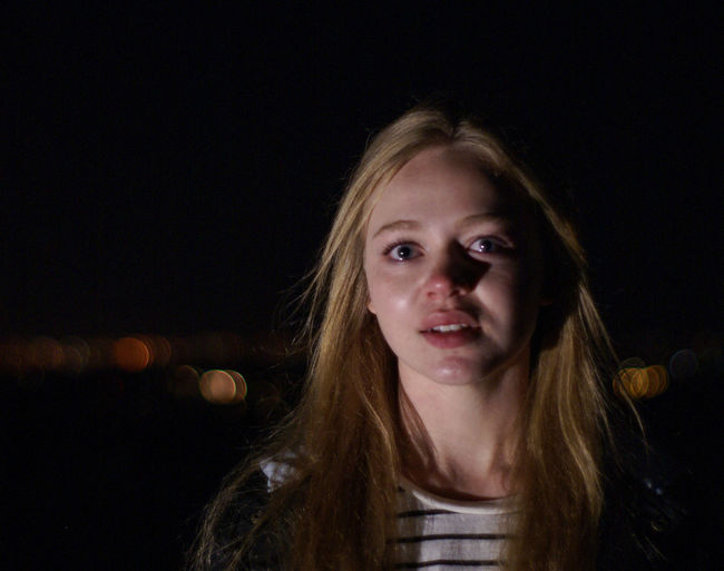 Portrait Of Young Woman With Teary Eyes At Night