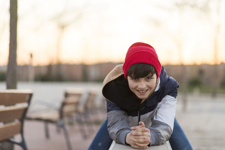 Young teenager portrait wearing a red hat Boys Childhood Close-up Day Elementary Age Focus On Foreground Front View Happiness Holding Leisure Activity Lifestyles Looking At Camera One Person Outdoors Portrait Real People Smiling Standing Waist Up Warm Clothing Water Young Adult