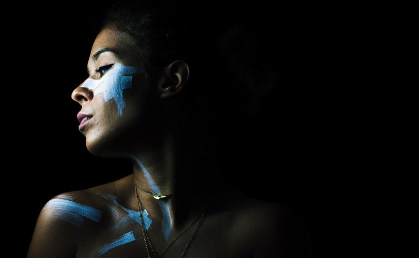 Woman with face paint against black background
