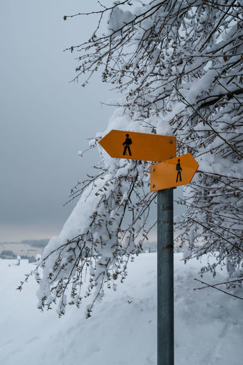 Road sign on snow covered field during winter