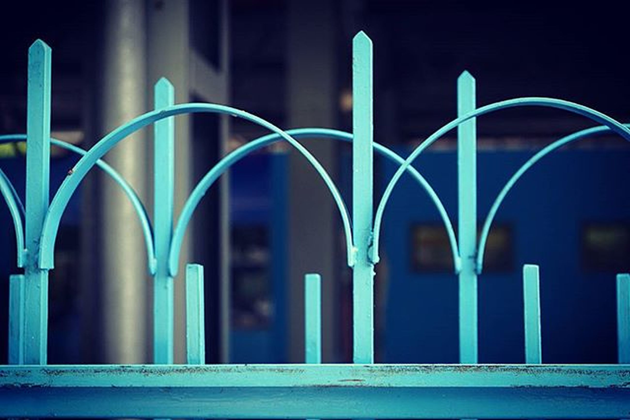 architecture, built structure, night, building exterior, blue, illuminated, arch, building, no people, outdoors, city, in a row, pattern, multi colored, window, circle, fence, gate, lighting equipment, railing