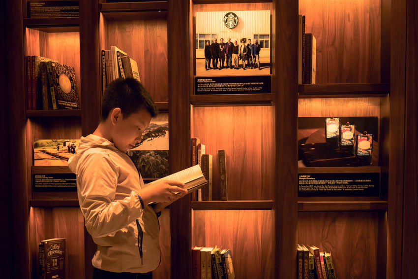Real People Indoors  Lifestyles Waist Up One Person Technology Leisure Activity Standing Casual Clothing Shelf Communication Men Child Young Adult Holding Side View Hairstyle Starbucks Reserve Roastery Shanghai Starbucks Coffee Reading Display