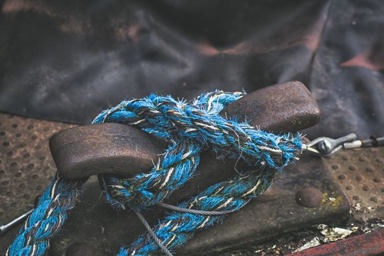 Close-up of blue rope tied on cleat