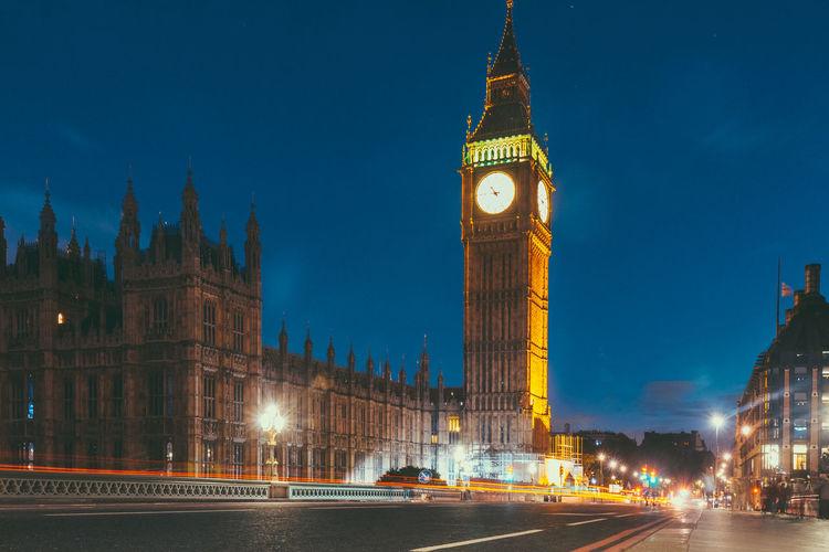 Illuminated clock tower in city at night