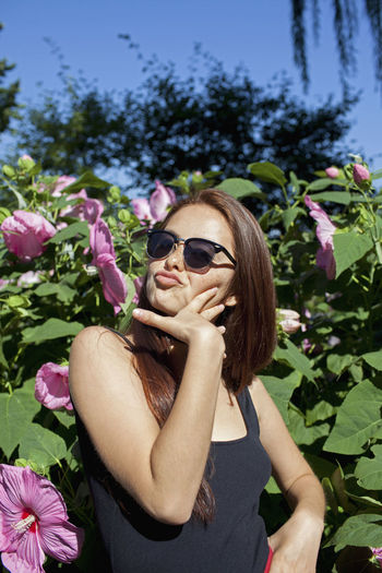 Young woman wearing sunglasses on pink flowering plants