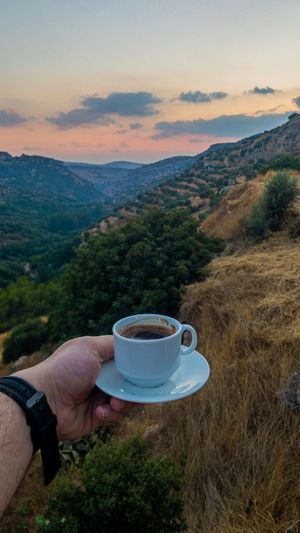 Man holding coffee cup against mountains and sky