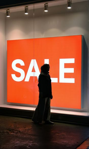 Silhouette Woman Standing By Sale Sign At Store