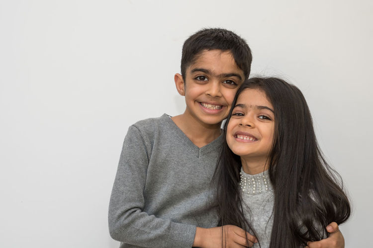 Portrait of smiling siblings standing against white background