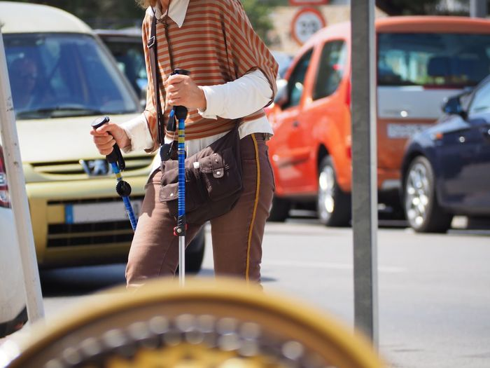 Midsection of man holding canes while walking on street against cars