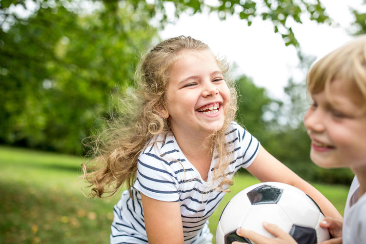 Smiling brother and sister playing with soccer ball in park