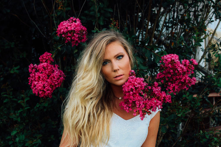 Portrait Of Beautiful Woman Standing With Pink Flowers