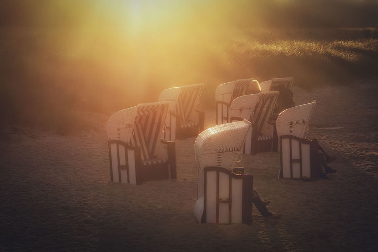 Some beach chairs during an evening in autumn at baltic sea Prerow Nature Land In A Row Seat Sunset Sky Outdoors Architecture Field Grass Absence Sunlight Built Structure Fog Environment Tranquility Beach Chairs Baltic Sea Sundown Dunes Beach Evening Light EyeEmNewHere Sunlight