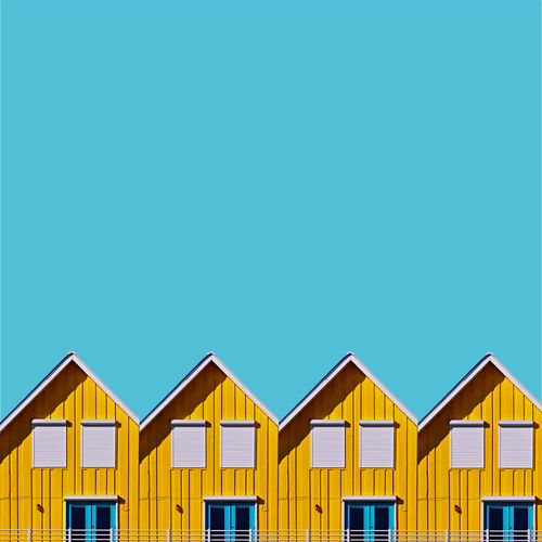 Beach huts against clear blue sky