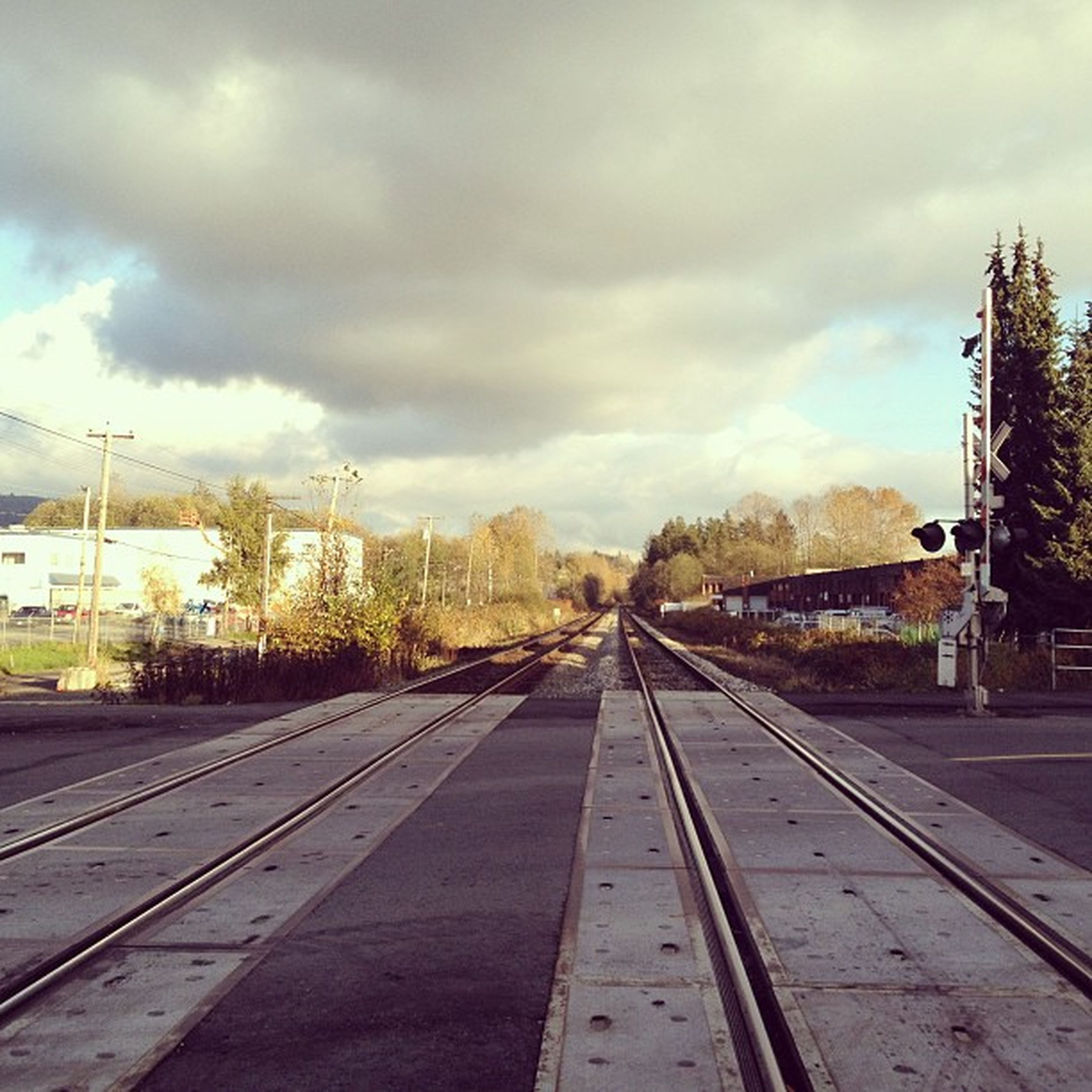 sky, cloud - sky, the way forward, transportation, cloudy, diminishing perspective, vanishing point, tree, cloud, road, built structure, building exterior, weather, architecture, street, railroad track, road marking, outdoors, overcast, day