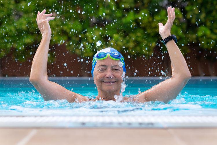 Portrait of happy senior woman swimming in pool