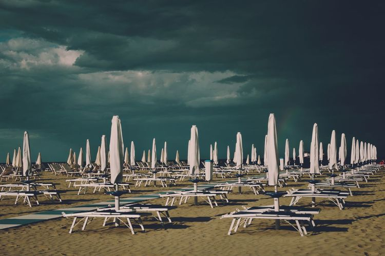 Long chairs and beach umbrellas against dramatic sky