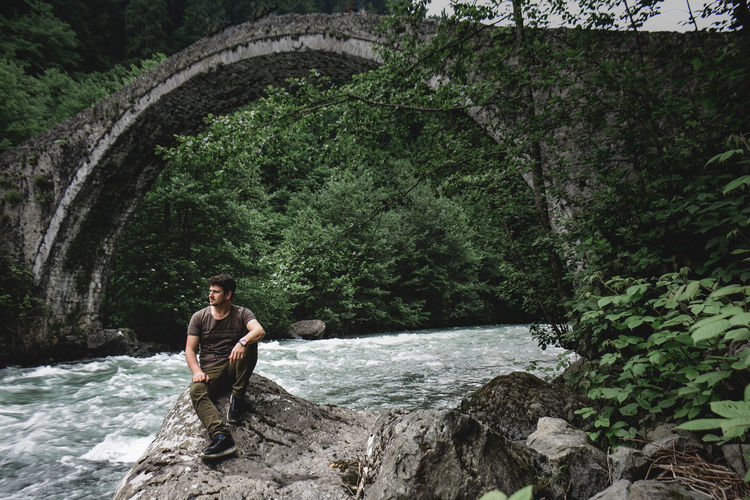 Man standing on rock by river