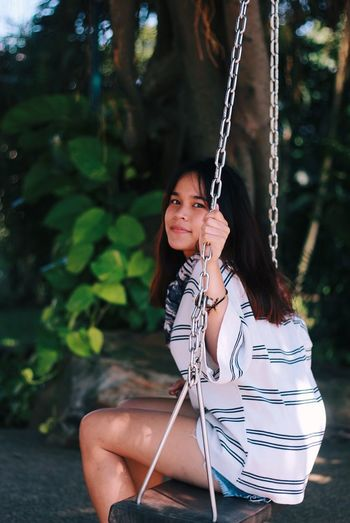 Portrait of young woman sitting on swing against tree