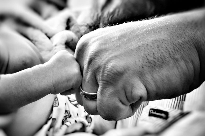 Cropped Image Of Father And Baby Boy Doing Fist Bump