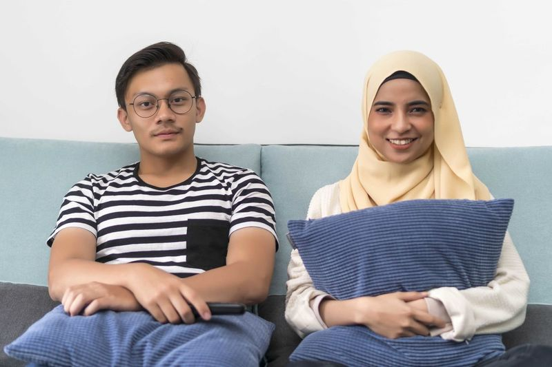 Young Malay Couple at the Sofa watching tv together Sitting Front View Casual Clothing Indoors  Lifestyles Child Looking At Camera Young Adult Portrait Leisure Activity Smiling People Males  Three Quarter Length Boys Young Women Striped Real People Men Togetherness Teenager Teenage Boys
