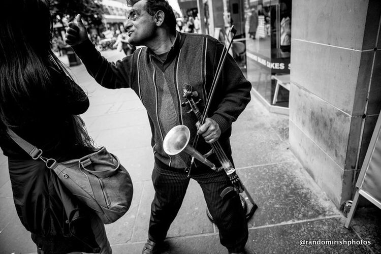 The Moment - 2014 EyeEm Awards this is the moment a busker in Glasgow explains to another amateur street photographer why they have to pay to take his picture . Determined to get my money's worth, I took this after I had paid my £5. Eye4photography  The Street Photographer - 2014 EyeEm Awards Blackwhitephotography