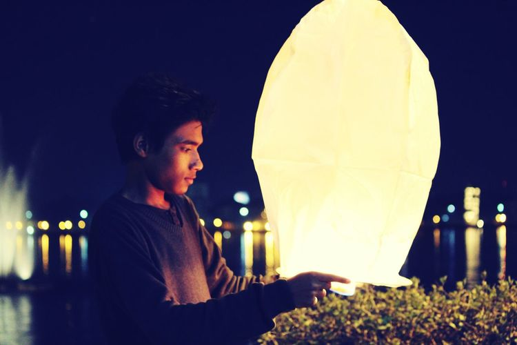 Young man holding illuminated paper lantern during diwali at night