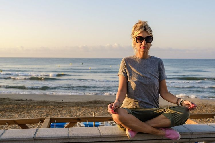 Portrait of mature woman meditating on seat at beach against sky