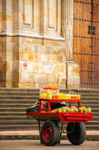 Fruits and juices for sale on cart against historic building at bolivar square
