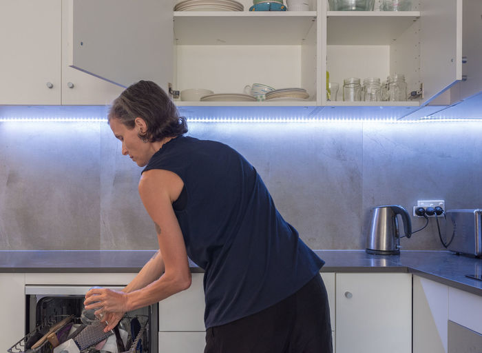 Woman unpacking dishwasher in modern kitchen One Person Indoors  Standing Sink Real People Side View Household Equipment Domestic Room Home Waist Up Lifestyles Casual Clothing Three Quarter Length Kitchen Looking Women Mature Women
