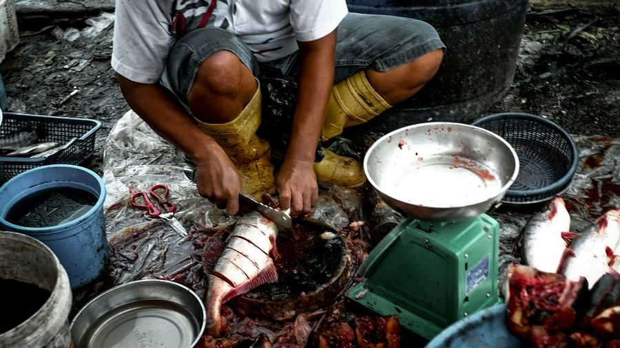 Low section of fish vendor cutting fish
