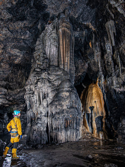 Woman standing against rock formations in cave