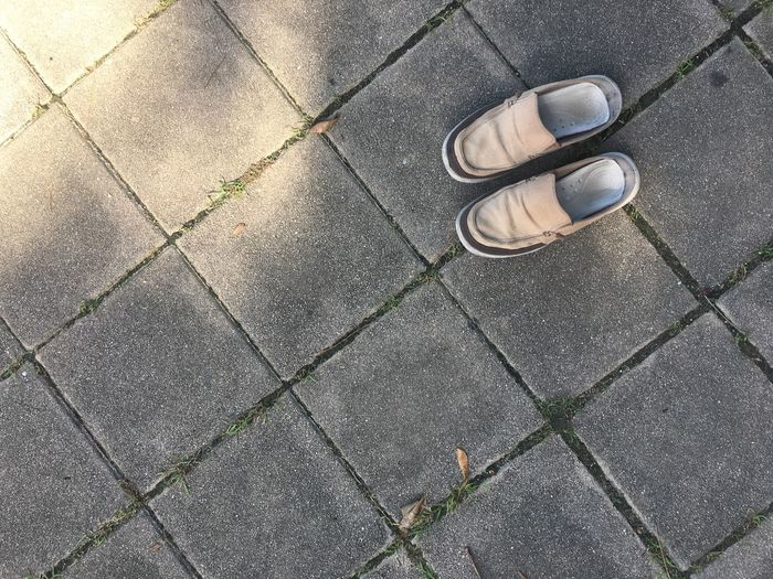Directly above shot of shoes on paving stones