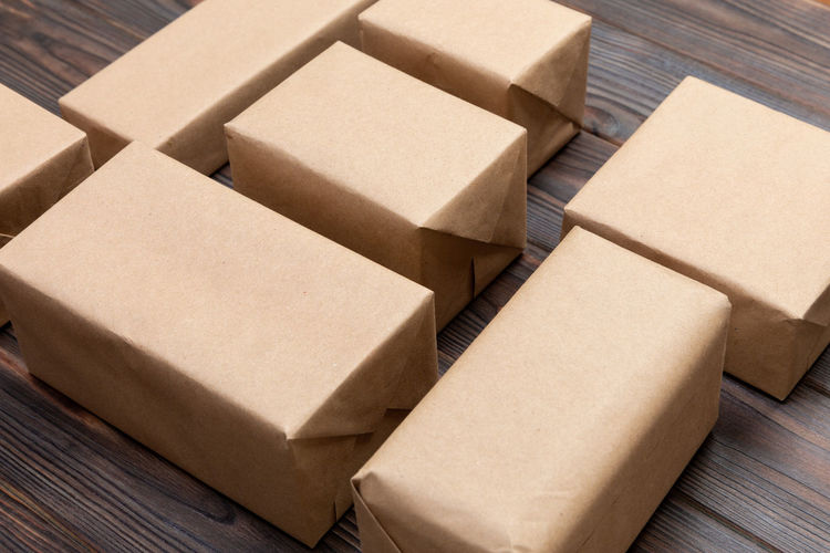 a lot of cardboard box on dark wooden background. top view Container Cardboard Box Box Cardboard Paper Box - Container Delivering Carton Brown Warehouse No People Indoors  Business Transportation Freight Transportation High Angle View Wood - Material Distribution Warehouse Close-up Packing Package Preparation  Receiving