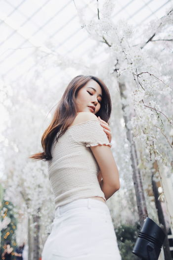 Low angle view of young woman standing against flowering trees at park