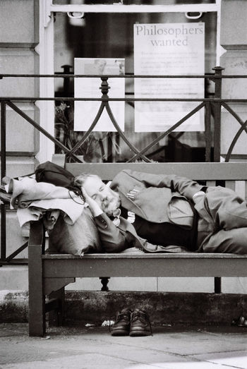 """I took the picture of this man taking a nap on a bench in Marylebone, London. The poste on the window reads """"Philosophers Wanted"""". Adult Lying Down Nap Philosopher Phylosophy Sleeping Street Photography The Street Photographer - 2017 EyeEm Awards"""