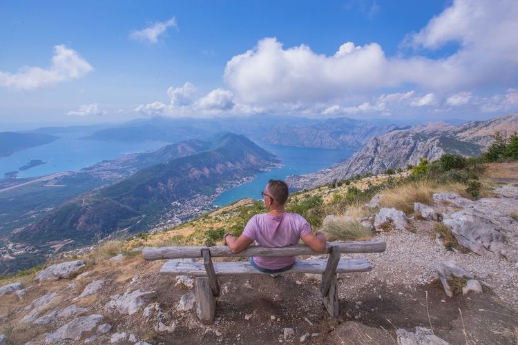 Rear view of man sitting on mountains against sky