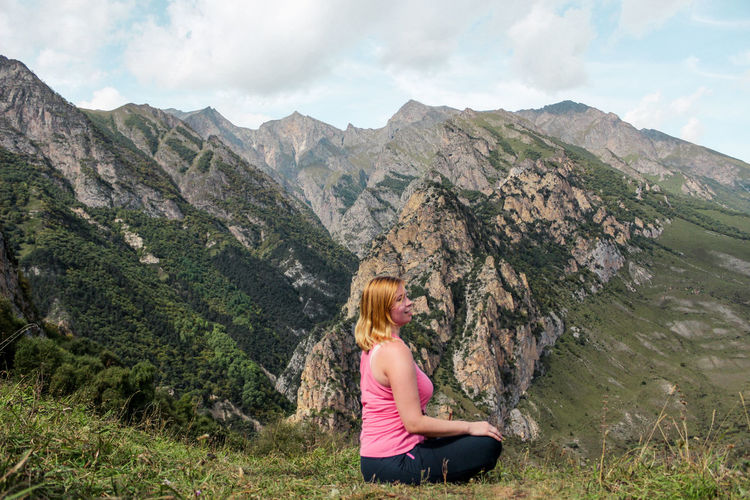 Side view of woman sitting against mountain range