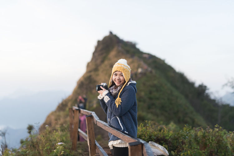 Portrait Of Smiling Woman Holding Camera Against Mountain