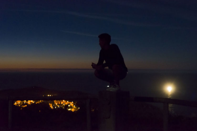 Silhouette man sitting in illuminated city against sky at sunset