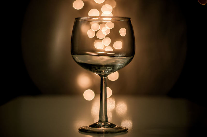 Close-up of wineglass against illuminated light