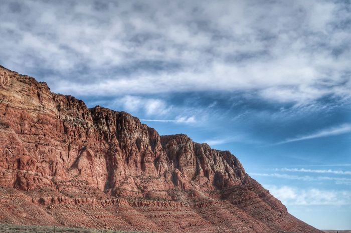 Low angle landscape of bare red cliff in Arizona Page Arizona Cloud - Sky Sky Nature Scenics - Nature Beauty In Nature Tranquility No People Rock - Object Mountain Low Angle View Rock Environment Day Non-urban Scene Solid Tranquil Scene Rock Formation Outdoors Mountain Range Land