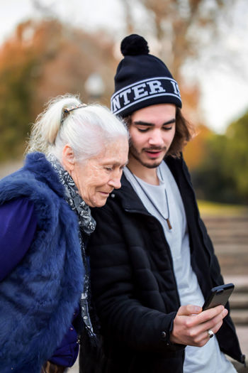 Pleasant young man explains to his elegant gray-haired grandmother how to use a smartphone. They walk in the autumn park and wear casual clothes. Mobile Phone Clothing Connection Wireless Technology Communication Real People Smart Phone Portable Information Device Technology Adult Focus On Foreground Lifestyles People Warm Clothing Leisure Activity Men Togetherness Women Outdoors Senior Adult Senior Women Elderly Grandma Grandson Bonding