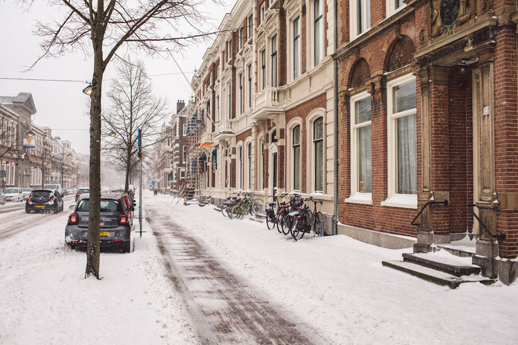 Cars on street amidst buildings in city during winter
