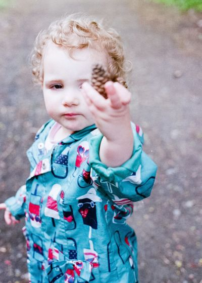 Cute baby girl holding pine cone standing outdoors