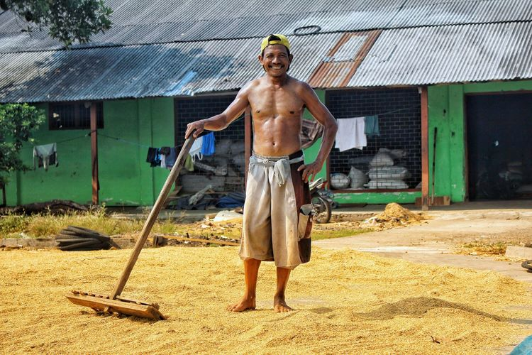 rice processor INDONESIA Jombang BeautyfullIndonesia Rice Processor Sportsman Muscular Build Full Length Sand Shirtless Men Standing Thatched Roof Parasol