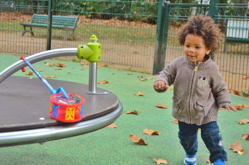 Cute girl playing with merry-go-round at playground