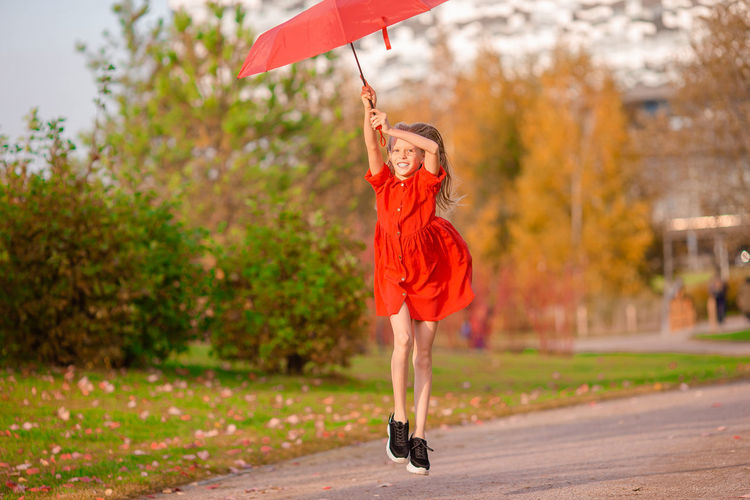 Full length of woman with red umbrella