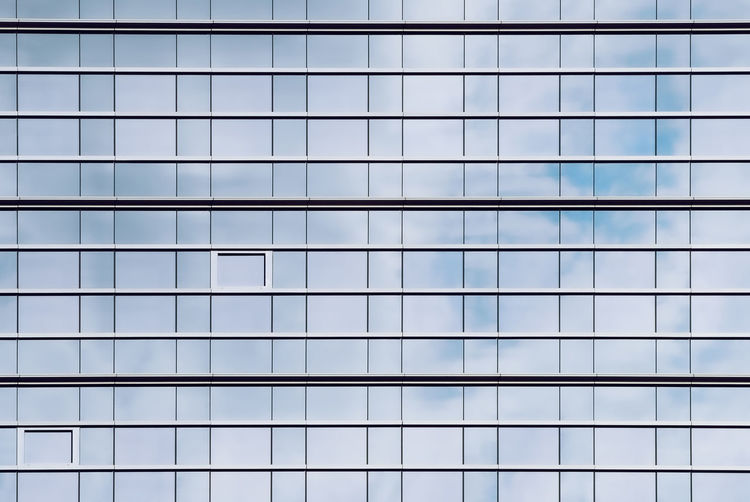 Glass facade of office buildings where the windows reflect the cloudy sky and create a perfect grid